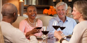 Smiling couples toasting wine glasses at dining room table