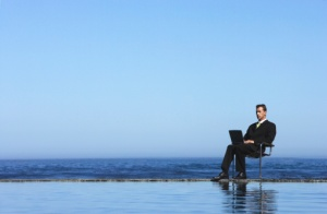 Businessman Using a Laptop Computer by the Sea
