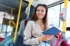woman-reading-book-bus-young-smiling-67647484